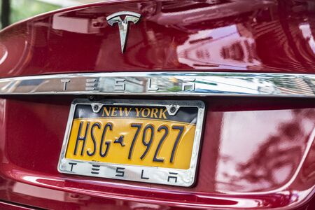 New York City, USA - August 3, 2018: Closeup of a red electric car Tesla parked on a street in New York City, USA