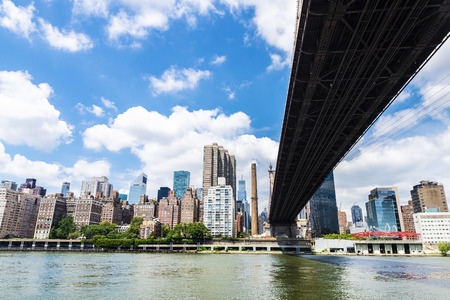 Low angle view of the Ed Koch Queensboro Bridge, also known as the 59th Street Bridge, seen from Roosevelt Island with the Manhattan skyline in New York City, USA