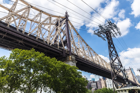 Low angle view of the Ed Koch Queensboro Bridge and a tower of tramway, also known as the 59th Street Bridge, seen from Roosevelt Island with the Manhattan skyline in New York City, USA Stock Photo