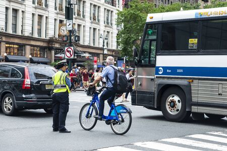 New York City, USA - July 31, 2018: Muslim woman police officer directing traffic on a street while a cyclist passes in Manhattan, New York City, USA