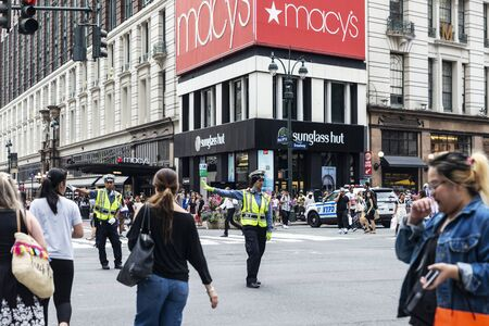 New York City, USA - July 31, 2018: Two policemen stopping the traffic raising your hand so that the people pass in front of Macys department store in Manhattan, New York City, USA