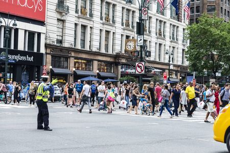 New York City, USA - July 31, 2018: Muslim woman police officer directing traffic raising your hand so that the people pass in front of Macys department store in Manhattan, New York City, USA Editorial
