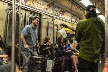 New York City, USA - July 31, 2018: Drummer and guitarist playing inside a subway car with people around in New York City, USA