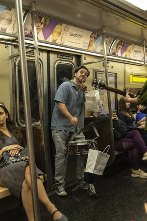 New York City, USA - July 31, 2018: Drummer and guitarist playing, waving and looking at camera inside a subway car with people around in New York City, USA