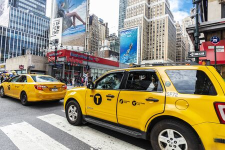 New York City, USA - July 31, 2018: Row of taxis on a street with people around and huge advertising screens in Manhattan, New York City, USA Foto de archivo - 127991959