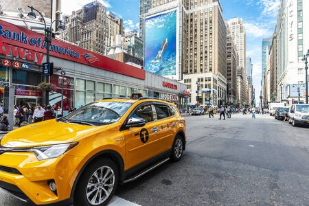 New York City, USA - July 31, 2018: Yellow taxi on a street with people around and huge advertising screens in Manhattan, New York City, USA Foto de archivo - 127991961