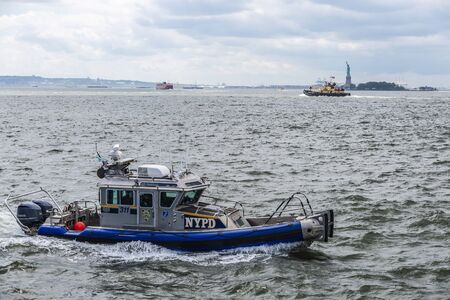 New York City, USA - August 1, 2018: NYPD police boat sailing along the coast in front of Statue of Liberty in New York City, USA Redactioneel