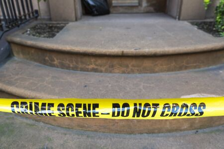 Yellow police tape with the text: crime scene do not cross at the entrance of a building in New York City, USA