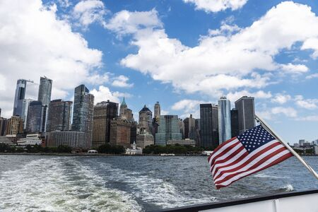 View of the skyline of modern skyscrapers of Manhattan with an American flag in New York City, USA 写真素材