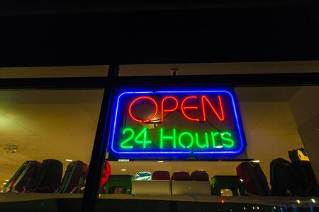 Neon sign of open 24 hours on a display shop at night in Harlem, Manhattan, New York City, USA
