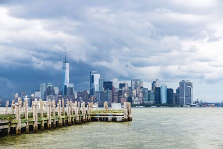 View of the skyline of modern skyscrapers of Manhattan from the Liberty Island pier in New York City, USA 写真素材