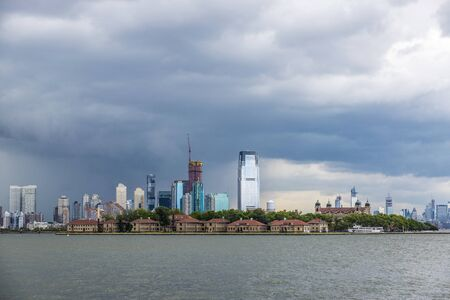 View of the skyline of modern skyscrapers of Jersey City and old buildings of Ellis Island in New York City, USA 写真素材