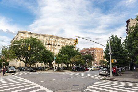 New York City, USA - August 2, 2018: Cross street with people around in Harlem, Manhattan, New York City, USA