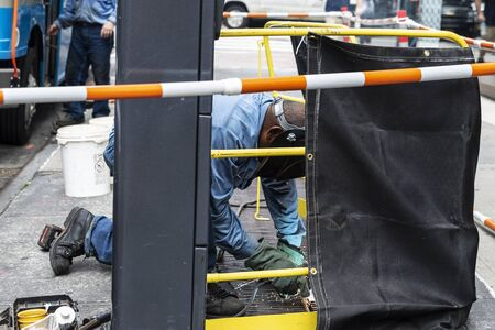 Welder doing a welding with goggles on a street in Manhattan, New York City, USA 写真素材