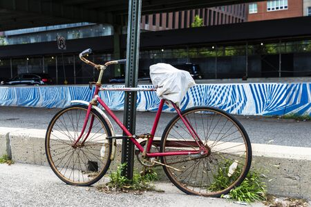 Old abandoned red bicycle next to road bridge next in Manhattan, New York City, USA