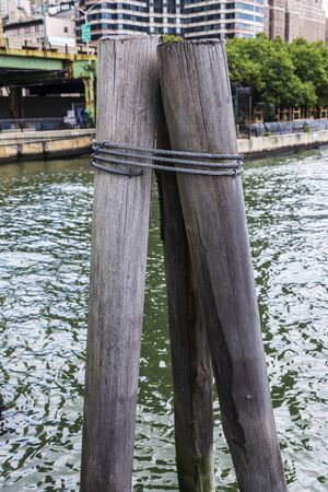 Old wooden pillar on a jetty of East River in Lower Manhattan, New York City, USA 写真素材