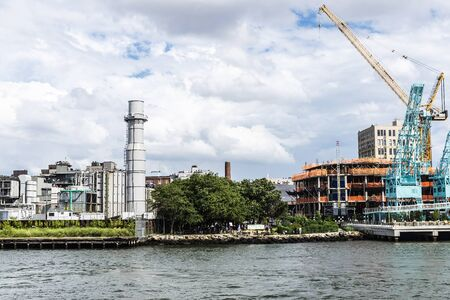 Construction of the Domino Park turning old factories into modern buildings, from East River in Brooklyn, New York City, USA
