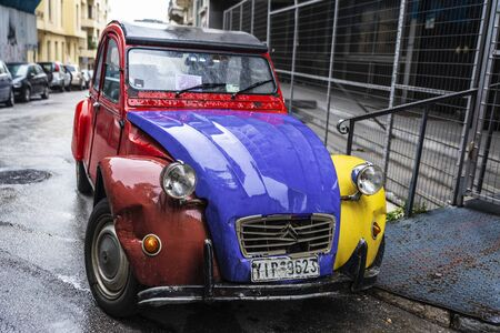 Athens, Greece - December 31, 2018: Red, yellow and blue Citroen 2CV (two steam horses or two tax horsepower) car parked on a street in Athens, Greece Editorial