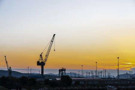 Backlight of harbor cranes at sunset and mountains in the background in Athens, Greece