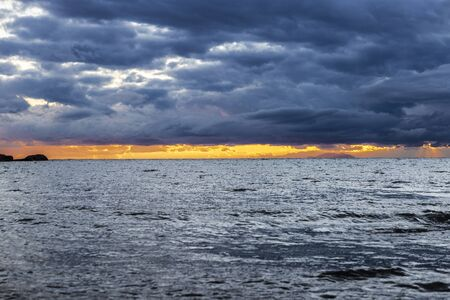 Cloudscape and the Aegean sea at sunset from the coast of East Attica in Greece as background