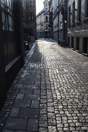 Calle pavimentada con un cartel del hotel al atardecer en el casco antiguo de Malmö con gente alrededor en Suecia