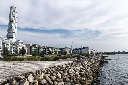Malmö, Sweden - August 30, 2019: Turning Torso, futurist skyscraper designed by Santiago Calatrava Street with modern residential buildings and the promenade by the sea in Västra Hamnen, Malmo, Sweden