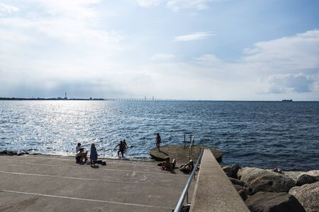 Malmö, Sweden - August 30, 2019: People sunbathing on the dike in the promenade in front of the Baltic Sea and the Öresund Bridge on summer in Västra Hamnen, Malmo, Sweden
