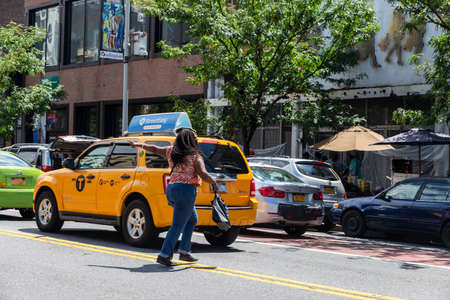 New York City, USA - August 4, 2018: Black woman crossing a street with traffic and pointing her finger in Harlem, Manhattan, New York City, USA