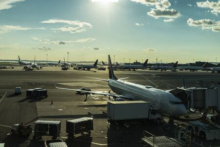 Workers loading and unloading goods in airplanes parked in a row at John F. Kennedy International Airport (JFK Airport, JFK or Kennedy) in Queens, New York City, USA