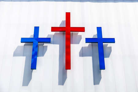Three blue and red crosses on a white wall in Harlem, Manhattan, New York City, USA Sajtókép