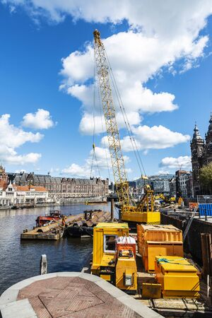 Heavy yellow crane on a pier of a canal in the centre of Amsterdam, Netherlands
