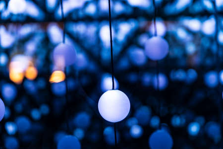 Many illuminated balls hung and linked by threads creating an infinite perspective as abstract blue background Stock Photo