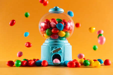 front view of a handful of gummy sweets with a candy machine dispenser, colors red, yellow, green, blue and pink.