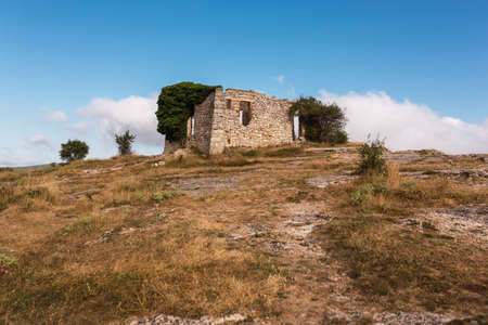 ruins of an old abandoned house in the mountain of La Mussara, tarragona, catalonia, spain. mountain, with blue sky and some clouds