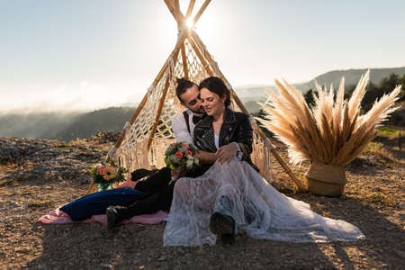 elopement wedding photo report, a couple of rock 'n' roll boyfriends. with a decorative teepee, bridal bouquet. cliffs, mountains and fog.