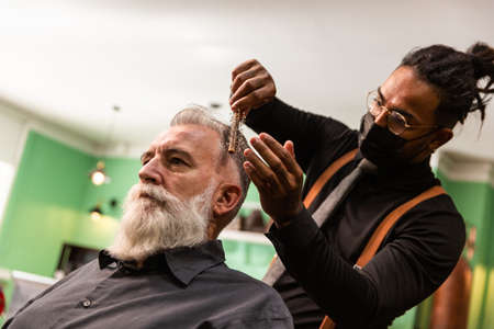 young african american barber and dreadlocks, with coronavirus pandemic prevention mask, combs with a comb and his hands a mature white caucasian man with a white gray beard in a barber shop. both hipster style