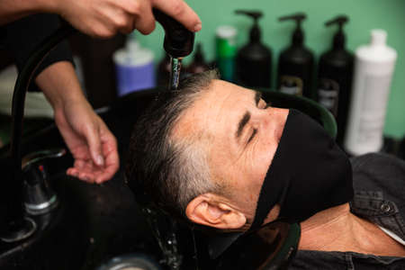 White Caucasian man with black mask of protection pandemic coronavirus is lying down while some barber's hands wash his hair with water and soap in hairdresser's, barber shop.
