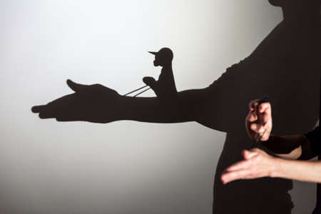 play shadow projected on a white screen. the person's hands shape the horse and rider