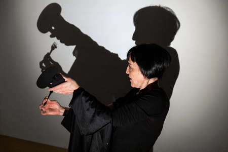 play shadow projected on a white screen. the person's hands shape a cook with a spoon or fork tasting food