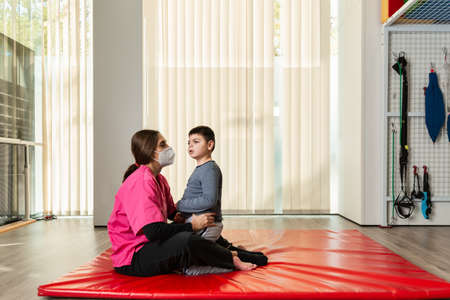 disabled child and physiotherapist on a red gymnastic mat doing exercises. pandemic mask protection