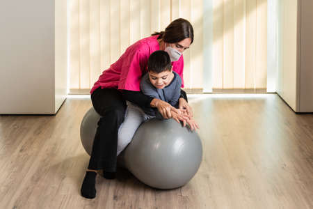 disabled child and physiotherapist on top of a Peanut Gym Ball doing balance exercises. pandemic mask protection