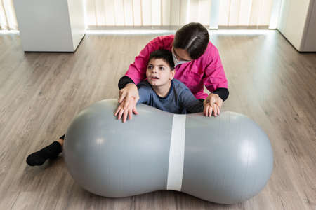 disabled child and physiotherapist on a Peanut Gym Ball doing balance exercises. pandemic mask protection