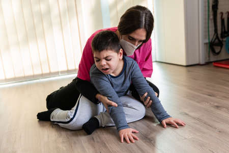 physiotherapist works with disabled child, cerebral palsy.
