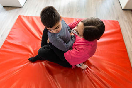 physiotherapy session of disabled child with a physiotherapist, they are hugged