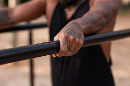 african american athlete boy does calisthenics fitness exercises on bars in park