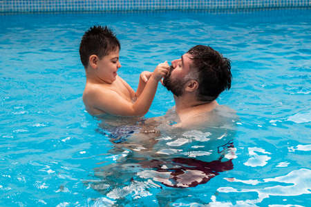 child with disability laughs and plays in his fathers arms in a swimming pool