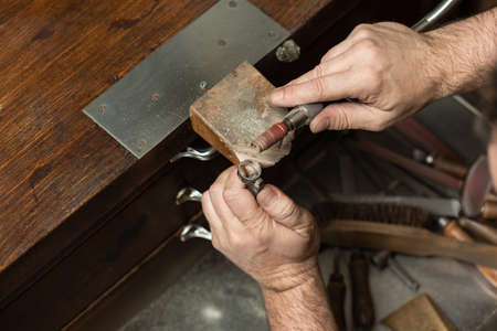 goldsmith sands a silver ring on the workbench.
