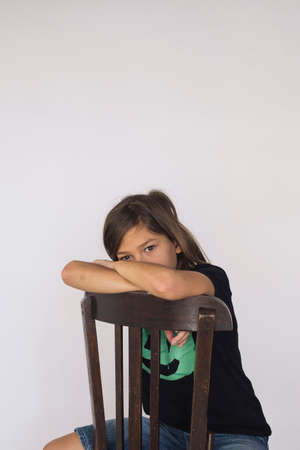 Eleven years old boy sitting on a wooden chair against a white background