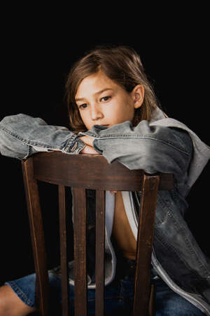 Eleven years old boy with hooded sweater and a jean jacket sitting on a wood chair against a black background