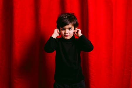 Three years old boy, wearing black clothes, crying against a red curtain Stockfoto